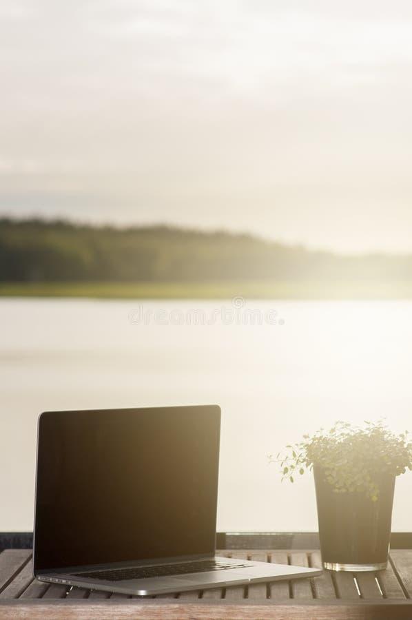 Eine entspannte und sentimentale Szene auf einem Balkon mit einem Laptop und einer Anlage auf einer hölzernen Terrassentabelle, n lizenzfreie stockbilder