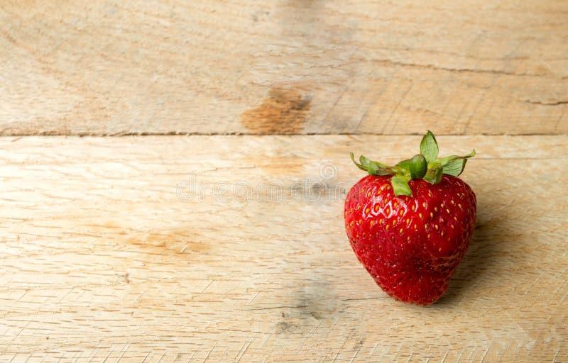 Eine Erdbeere auf rustikalem hölzernem Hintergrund stockfotos