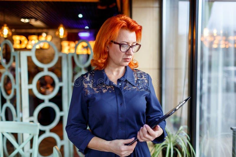 Eine ernste Frau mit dem roten Haar, Stände nahe einem Fenster und Griffe ein Klemmbrett lizenzfreie stockfotos