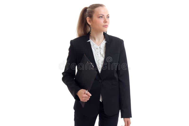 Eine ernste junge schöne Geschäftsfrau, die in einem schwarzen Anzug steht und ein Tablet hält stockfotos