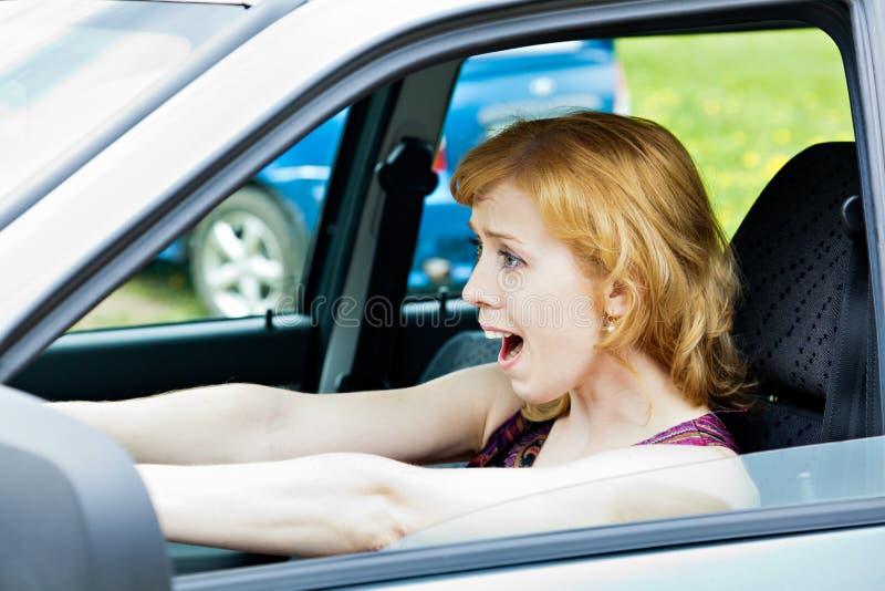 Eine erschrockene Frau hinter dem Rad stockbild