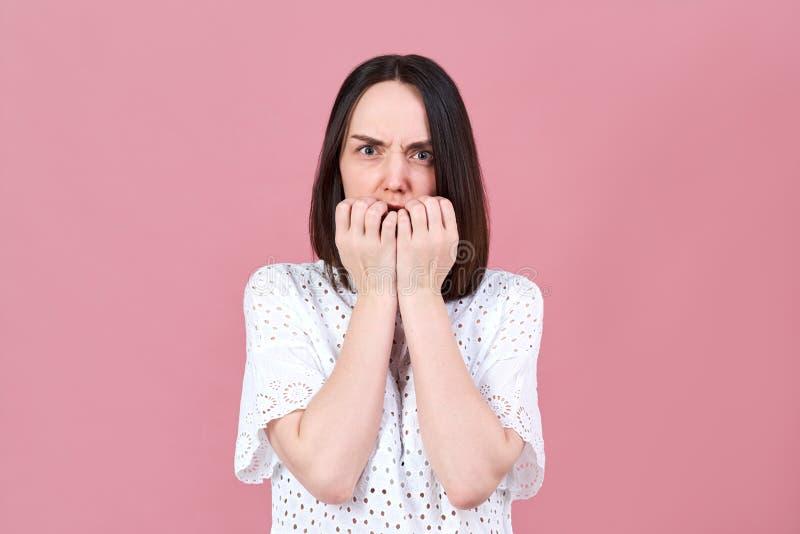 Eine erschrockene, verwirrte und die Stirn gerunzelte-oben junge Frau betrachtet eindrucksvoll der Kamera und drückt ihre Hände z stockbild