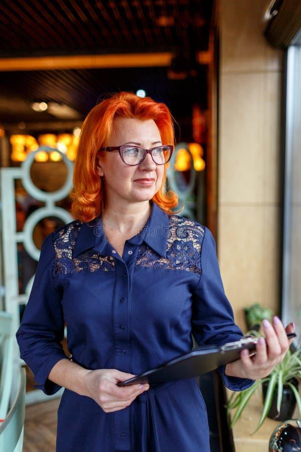 Eine erwachsene Frau in den Gläsern mit dem roten Haar, in den Ständen nahe einem Fenster und in den Griffen ein Klemmbrett in ih stockbilder