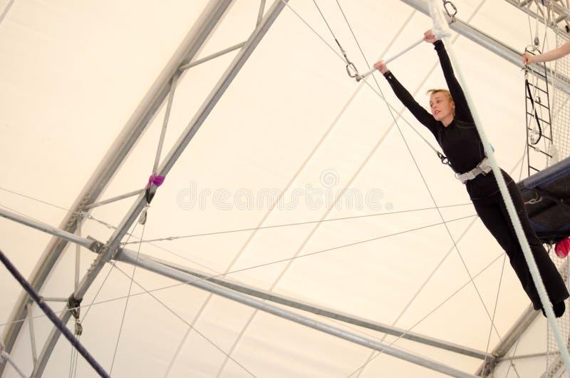 Eine erwachsene Frau hängt an einem fliegenden Trapez an einer Innenturnhalle Die Frau ist ein Amateurtrapezkünstler stockfoto