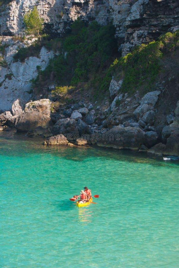 Eine Familie auf einem Kajak im kristallenen Meer von Menorca stockbilder