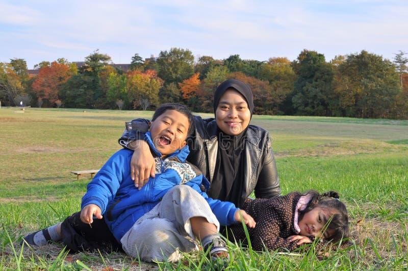 Eine Familie, die auf Gras während des Herbstes liegt und sitzt stockfoto