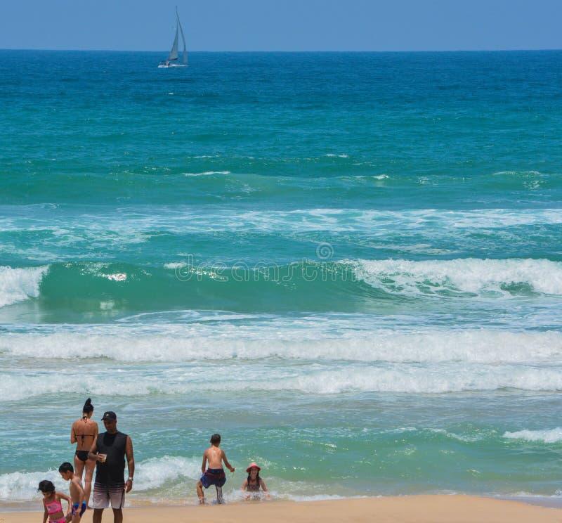 Eine Familie, die im Sand und in den Wellen des Mittelmeeres bei Ashkelon, Israel spielt lizenzfreies stockfoto