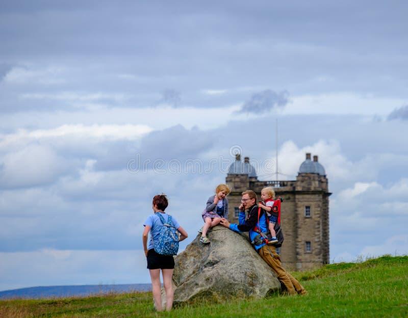 Eine Familie erholt sich auf einem Felsen auf einem Hügel im Lyme Park mit dem Cage Turm im Hintergrund lizenzfreie stockfotografie