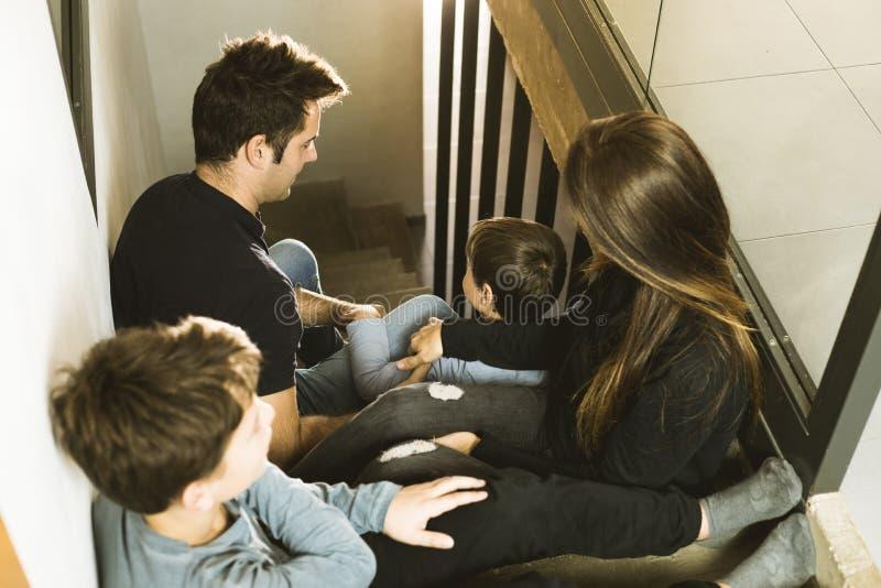 Eine Familie mit den Kindern, die zu Hause auf der Treppe glücklich und dem Lächeln sitzen Entzückende Paare mit Kindern zu Hause stockfotografie