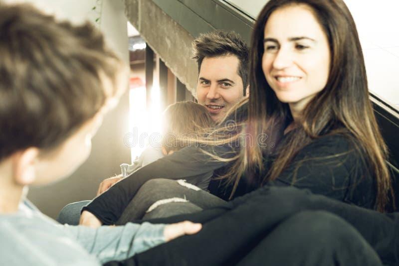 Eine Familie mit den Kindern, die zu Hause auf der Treppe glücklich und dem Lächeln sitzen Entzückende Paare mit Kindern zu Hause lizenzfreie stockfotografie