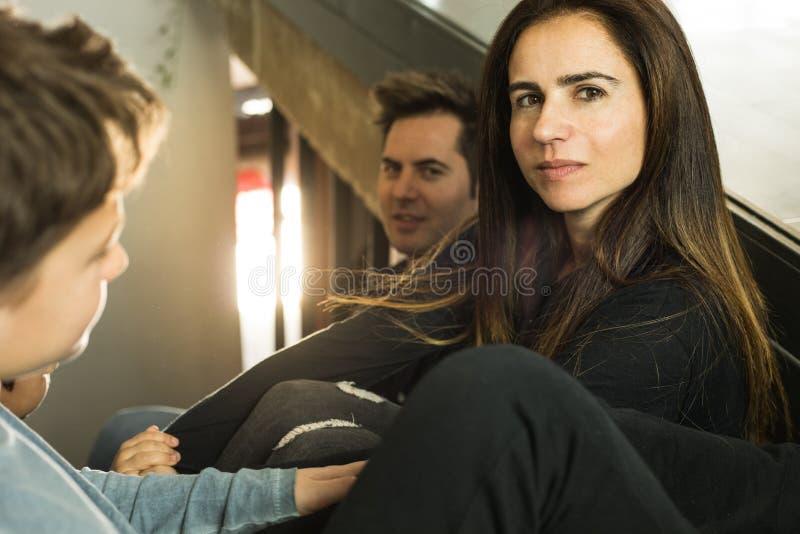 Eine Familie mit den Kindern, die zu Hause auf der Treppe glücklich und dem Lächeln sitzen Entzückende Paare mit Kindern zu Hause stockfotos