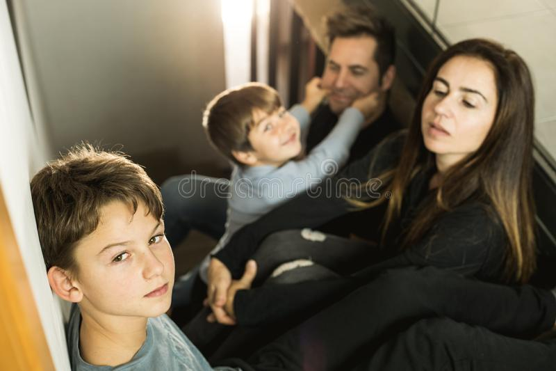 Eine Familie mit den Kindern, die zu Hause auf der Treppe glücklich und dem Lächeln sitzen Entzückende Paare mit Kindern zu Hause lizenzfreie stockbilder