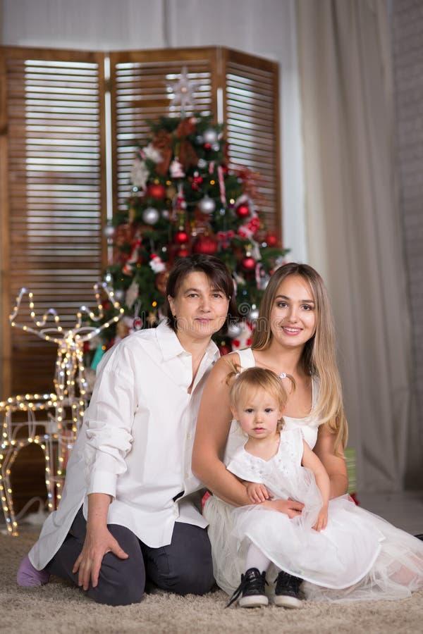 Eine Familie mit einem Baby sitzt das Sitzen nahe dem Weihnachtsbaum lizenzfreie stockfotos