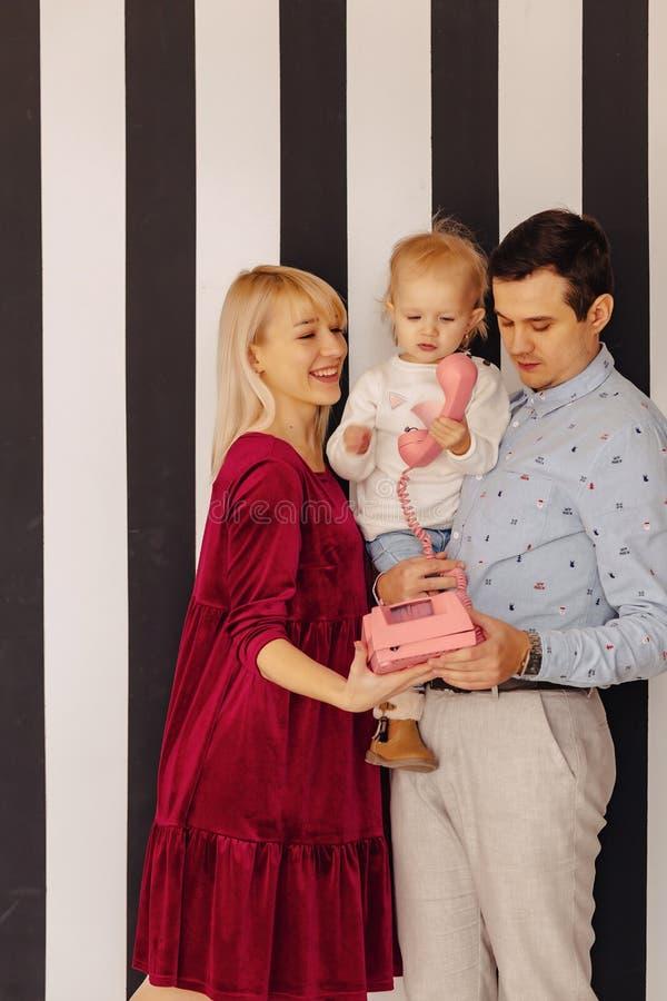 Eine Familie mit einer kleinen Tochter, die durch rosafarbenes Retro- Telefon, einen einfachen Hintergrund, Glück und Freude spri stockbild