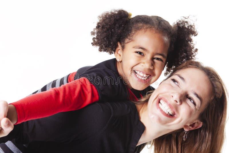 Eine Familienmutter mit dem Mädchenkind, das auf einem weißen Hintergrundstudio aufwirft stockfoto