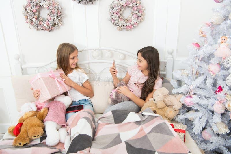 Eine Feiertagsbildmitteilung Machen des Weihnachts- und des neuen Jahresfotos mit Smartphone Glückliche kleine Kinder mit Handy stockbild