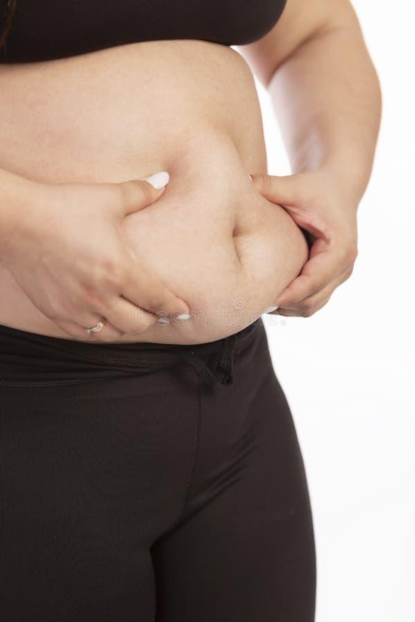 Eine fette Frau ergreift ihren Bauch mit ihren Händen, Nahaufnahme stockfotos
