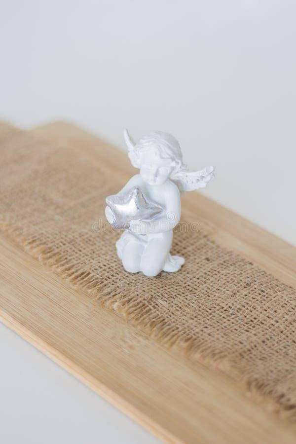Eine Figürchen ist ein Engel auf hölzernem backgroun stockfotografie