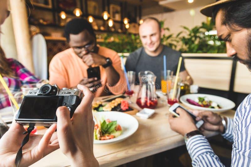 Eine Firma von den multikulturellen jungen Leuten in einem Caf? Pizza, trinkende Cocktails essend, Spa? habend lizenzfreie stockfotos