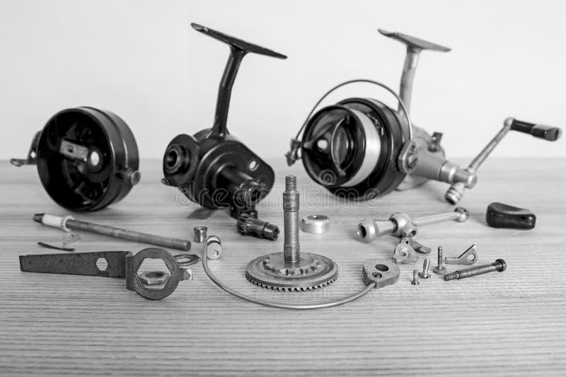 Eine Fischereispinnende Spule als Ganzes und ein zweites ähnliches vollständig auseinandergebaut Fase gezeichnet unter Verwendung lizenzfreies stockbild
