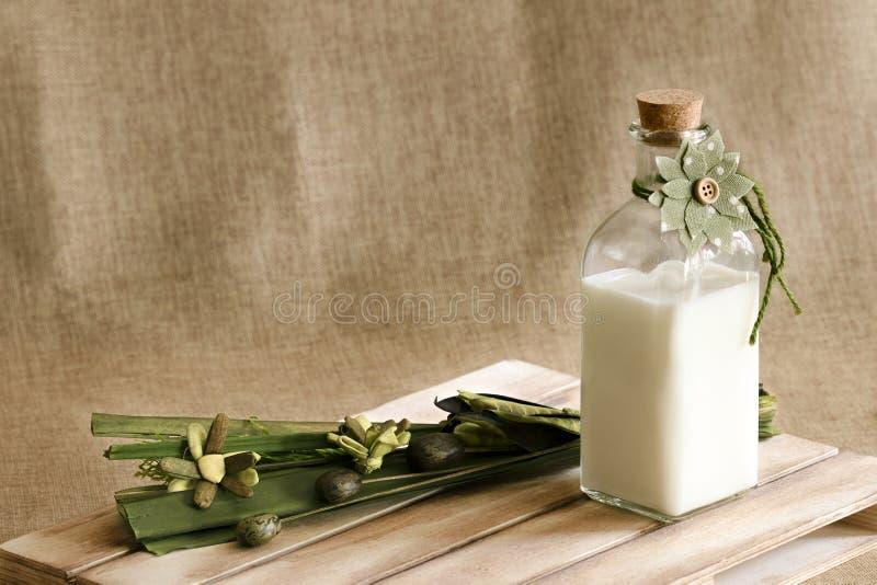 Eine Flasche der frischen Milch und irgendeiner Blumendekoration stockfotos
