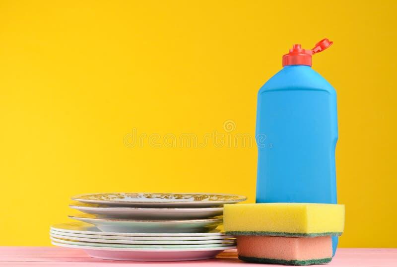 Eine Flasche der Tellerreinigung, Schwämme, Geräte auf einer hölzernen Pastellfarbtabelle gegen einen gelben Wandhintergrund, Kop stockbilder