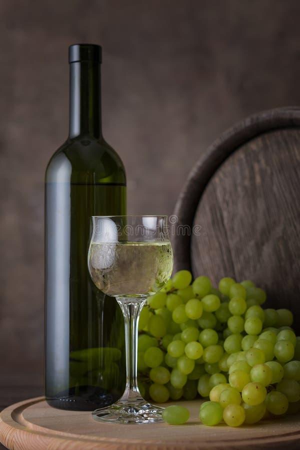 Eine Flasche des Weißweins, des Glases Weißweins auf einem Hintergrund von Trauben und des Fasses auf Holztisch stockbild