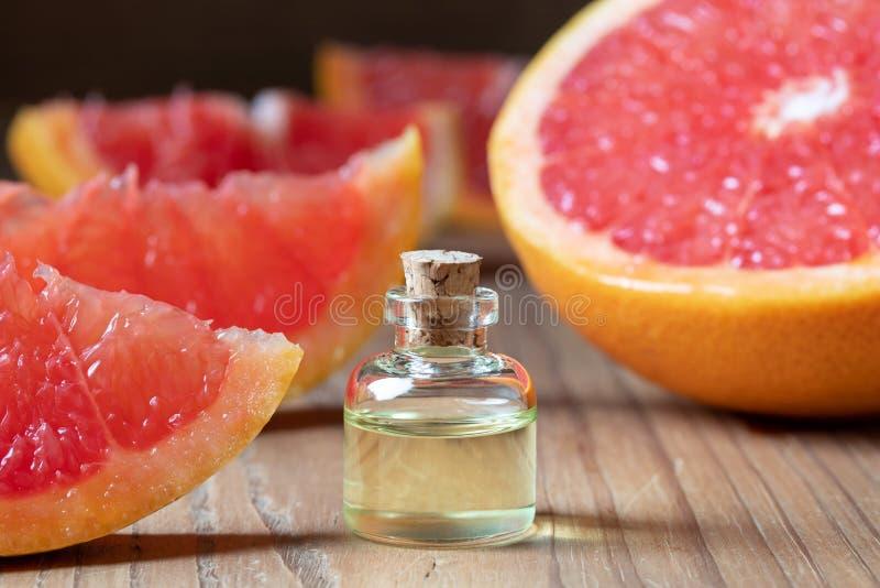 Eine Flasche Grapefruitkernöl mit frischer rosa Pampelmuse auf einer Tabelle stockfoto