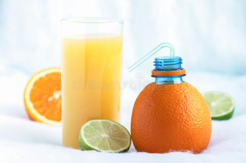 Eine Flasche hergestellt von der natürlichen Orange und von einem Glas frisch zusammengedrücktem Orangensaft umgeben durch Scheib stockfotos