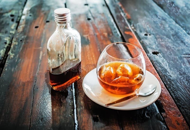 Eine Flasche kalter Gebräukaffee und und Eis im Glas mit vorbereitetem kaltem Gebräugetränk stockfotos