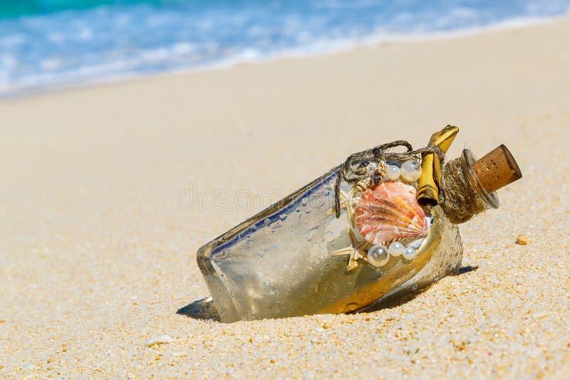 Eine Flasche mit einer Mitteilung, die das Meer auf dem Sand eines tro machte lizenzfreie stockbilder