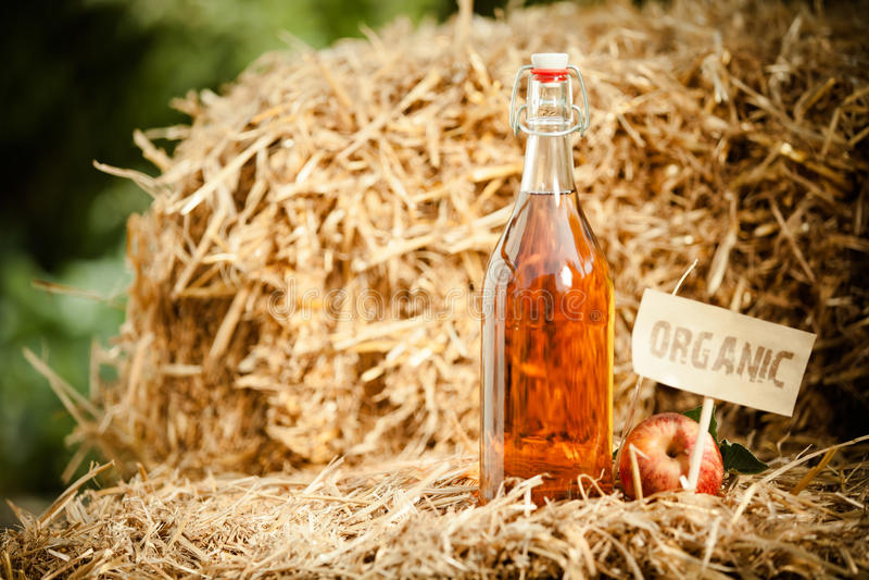 Eine Flasche natürlicher Apfelweinessig auf Stroh lizenzfreie stockfotos