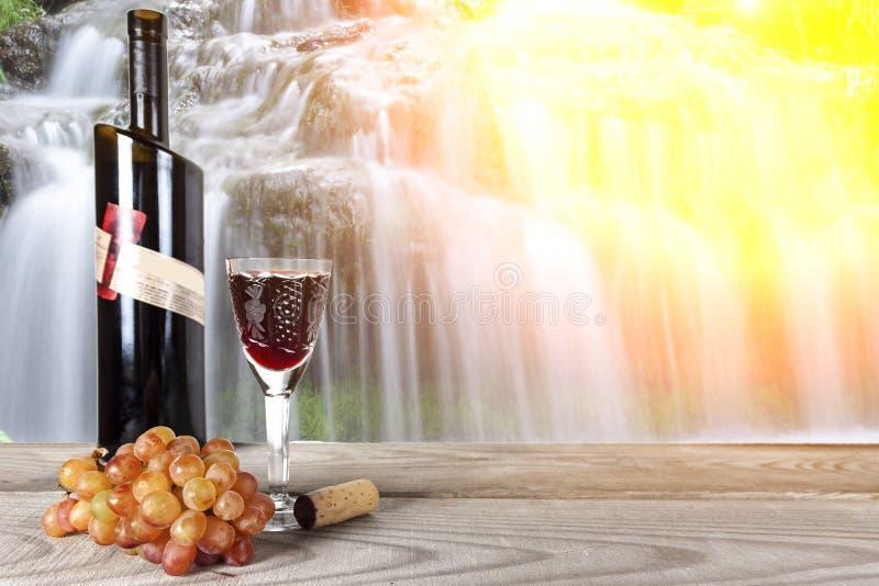 Eine Flasche Wein mit einem Weinglasstand auf einem hölzernen Brett vor dem hintergrund eines Wasserfalls stockbild