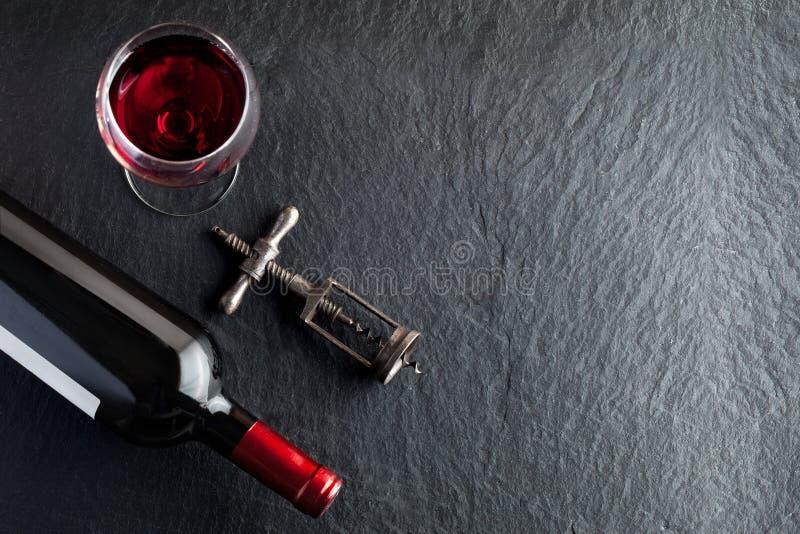 Eine Flasche Wein neben dem Glas und der Korkschraube stockbild