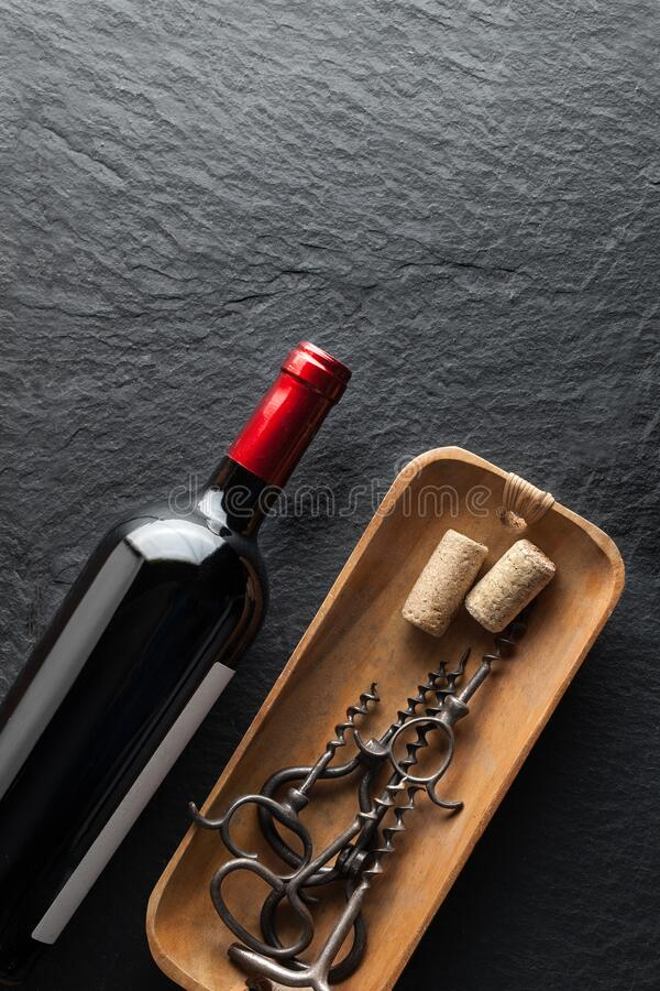 Eine Flasche Wein neben den Korkschrauben Eine Flasche Wein neben den Korkschrauben Eine Flasche Wein neben den Korkschrauben lizenzfreie stockbilder