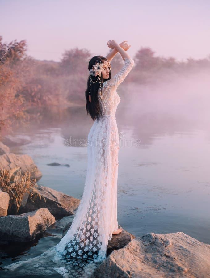 Eine Flussnymphe in einem weißen Spitzekleid steht auf einem Felsen durch den See Die Prinzessin hat einen schönen Kranz mit Musc stockbild