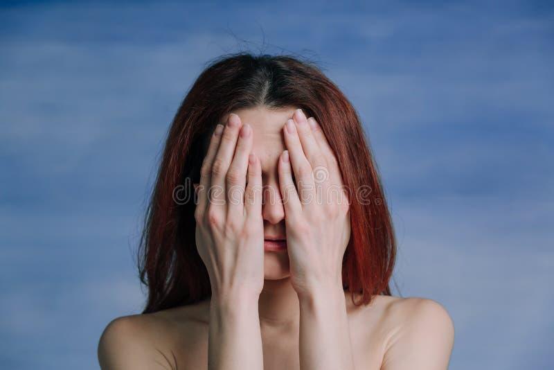 Eine Frau bedeckte ihr Gesicht mit ihren Händen stockbilder