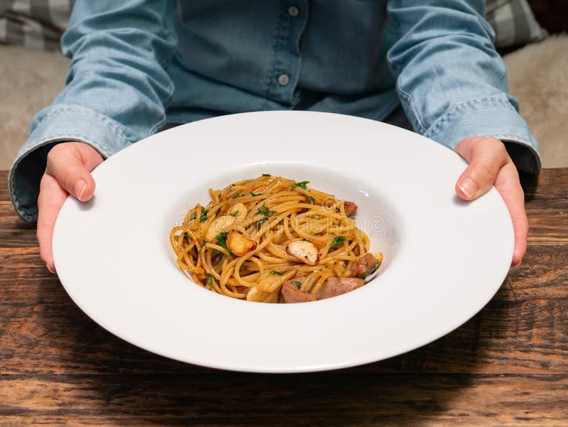 Eine Frau benutzt Hände zum Halten und zur Übergebung eines Tellers der würzigen Spaghettis mit Schweinswurst und Knoblauch in de stockfotos