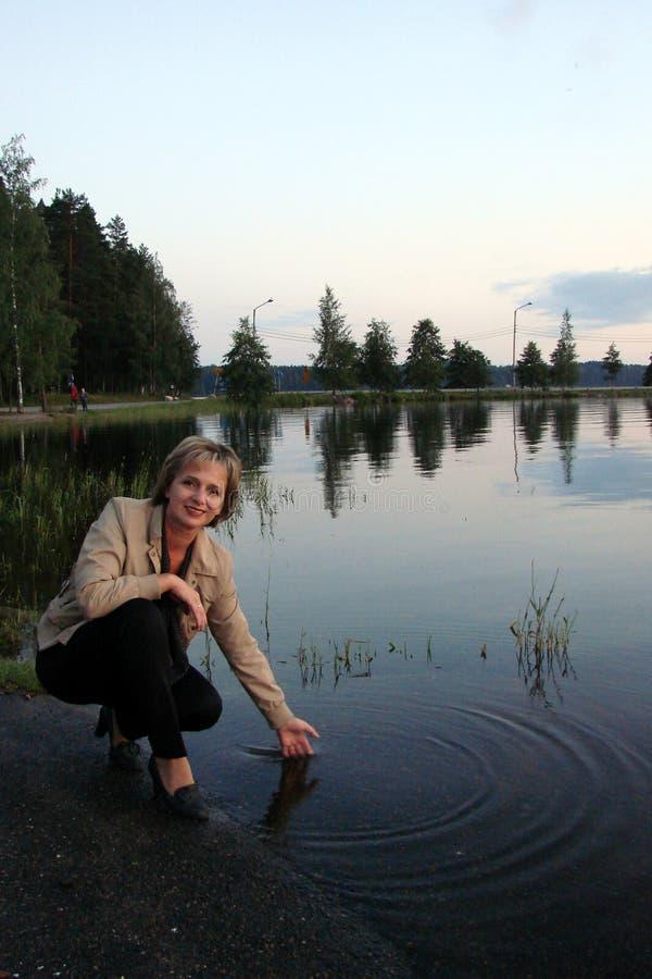 Eine Frau berührt das Wasser lizenzfreie stockfotografie