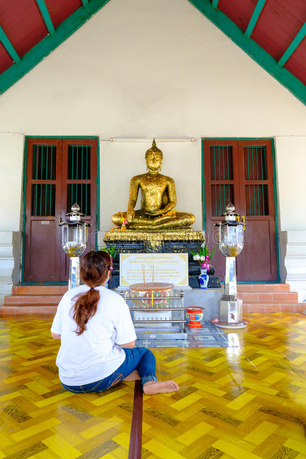Eine Frau betet zu Buddha-Statue stockfoto