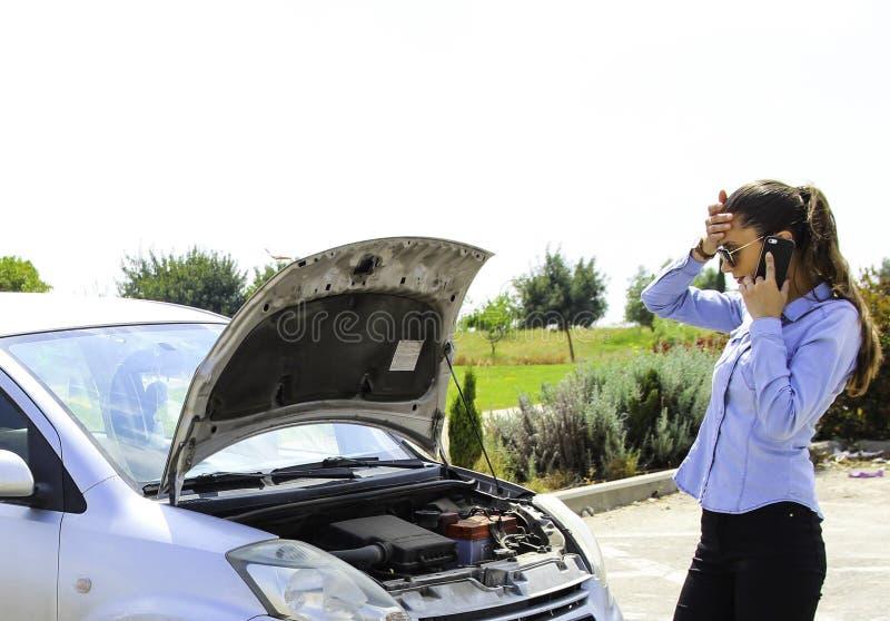 Eine Frau bleibt ein defektes Auto, Bedarf helfen, das Auto motiviert nicht stecken lizenzfreie stockfotografie