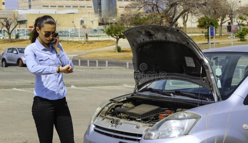 Eine Frau bleibt ein defektes Auto, Bedarf helfen, das Auto motiviert nicht stecken lizenzfreie stockbilder