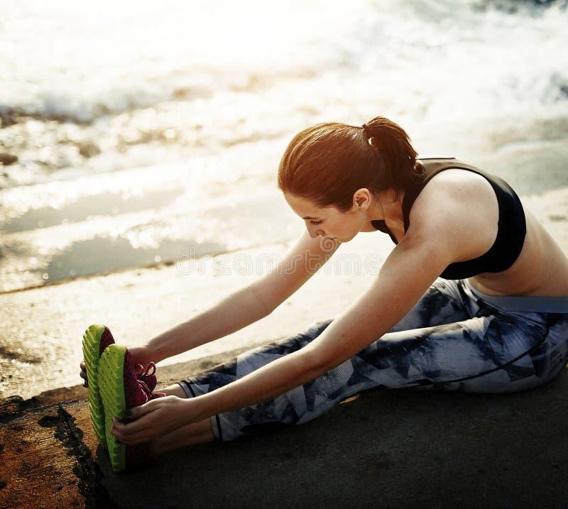 Eine Frau dehnt am Strand aus stockbilder