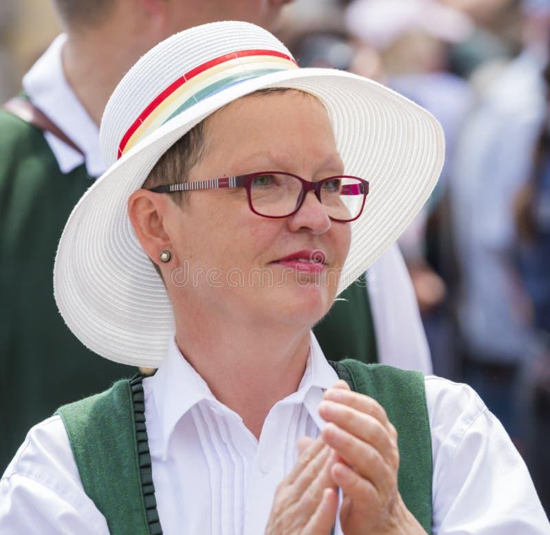 Eine Frau in der typischen bayerischen Kleidung und in einem Hut, der an dem Schwulenparade-alias Christopher Street Day CSD in M lizenzfreie stockbilder