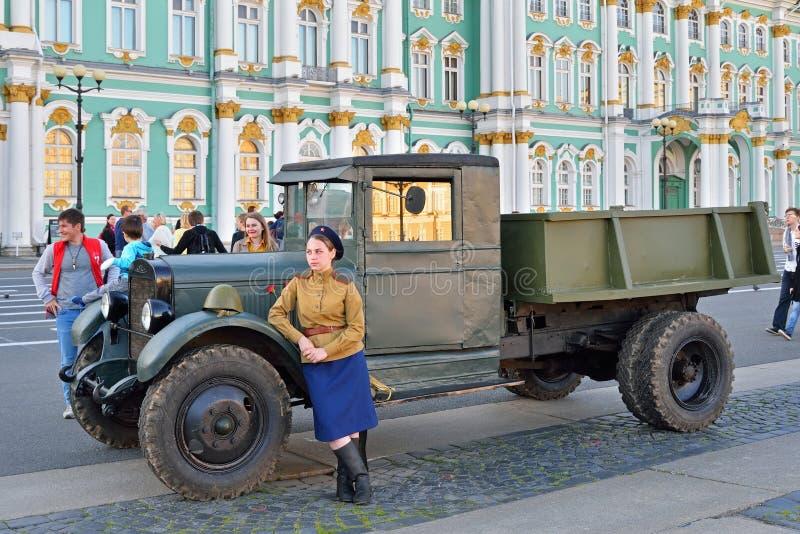 Eine Frau in der Uniform während des Zweiten Weltkrieges lehnte sich auf dem Auto ZIS an stockbild
