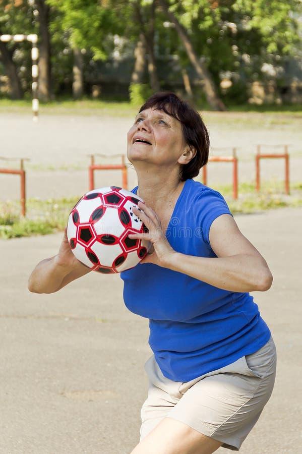 Eine Frau des Pensionsalters wirft den Ball in einem Basketballkorb lizenzfreie stockfotografie