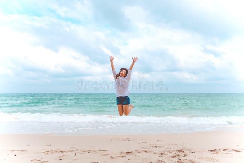 Eine Frau, die auf den Strand vor dem Meer mit dem Fühlen glücklich springt stockbilder