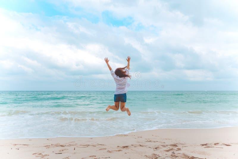Eine Frau, die auf den Strand vor dem Meer mit dem Fühlen glücklich springt lizenzfreies stockbild