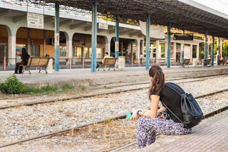 Eine Frau, die auf der Plattform Larissa Train Stations sitzt lizenzfreies stockbild