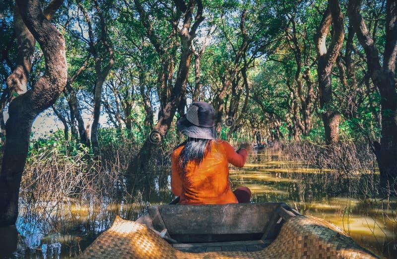 Eine Frau, die auf ein Boot im Dorf errichtet auf dem Tonle Sap See schwimmt lizenzfreie stockfotos
